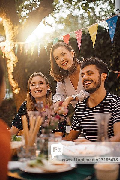 Glückliche junge Freunde und Freundinnen bei Tisch während der Dinnerparty im Hinterhof