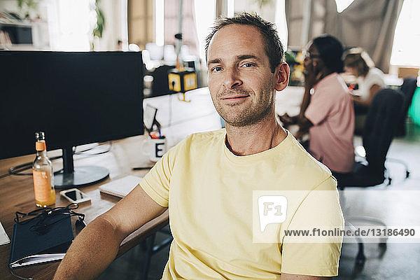 Porträt eines selbstbewussten Geschäftsmannes  der in einem kreativen Büro sitzt