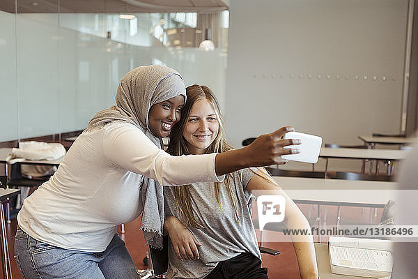 Smiling woman in hijab taking selfie with friend on smart phone at classroom