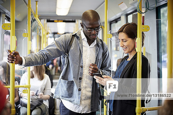 Multi-ethnic commuters sharing smart phone while standing in tram