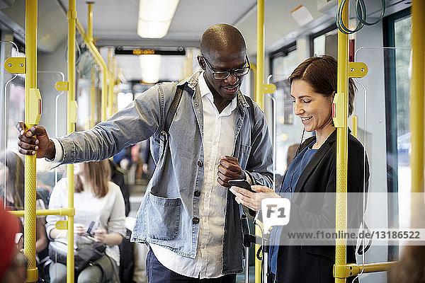 Multi-ethnische Pendler  die sich ein Smartphone teilen  während sie in der Straßenbahn stehen