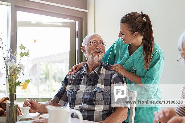 Älterer Mann spricht mit Krankenschwester beim Frühstück im Pflegeheim