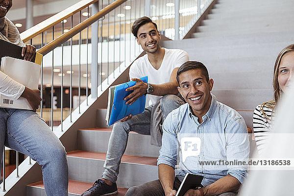Lächelnde Highschool-Schüler sprechen auf Stufen auf dem Campus