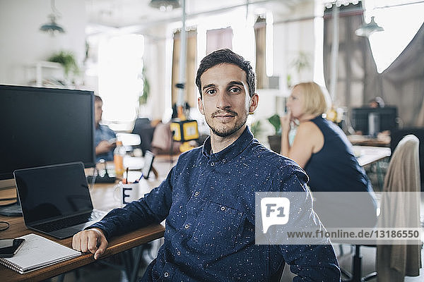 Porträt eines selbstbewussten jungen Geschäftsmannes  der am Schreibtisch im Kreativbüro sitzt