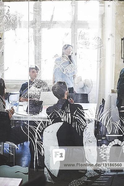Geschäftsleute im Sitzungssaal durch gemustertes Glas im Kreativbüro gesehen