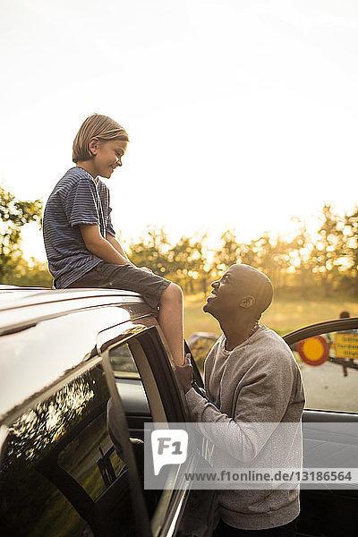Lächelnder Mann schaut ein Mädchen an  das bei Sonnenuntergang auf dem Autodach sitzt