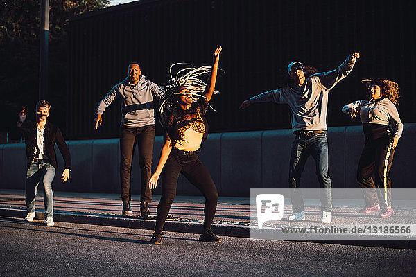 In voller Länge multiethnische männliche und weibliche Freunde tanzen auf dem Bürgersteig in der Stadt