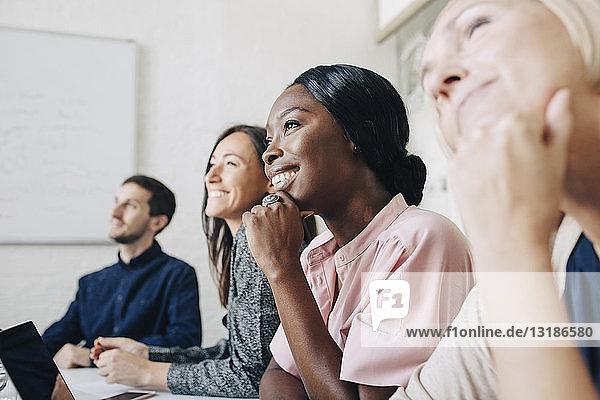 Lächelnde multiethnische Geschäftsleute hören zu  während sie während einer Sitzung im Sitzungssaal sitzen