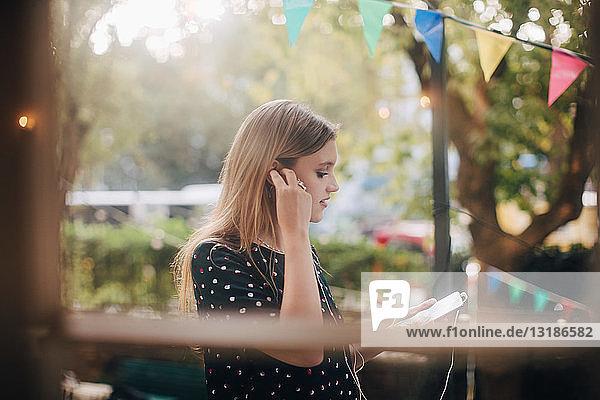 Junge Frau beim Anpassen von Kopfhörern während der Benutzung eines Mobiltelefons auf dem Balkon während einer Party