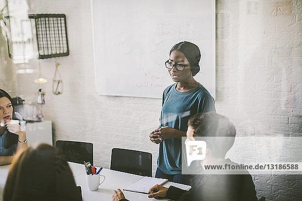 Kreative Geschäftsfrau erklärt Kollegen während einer Sitzung im Sitzungssaal