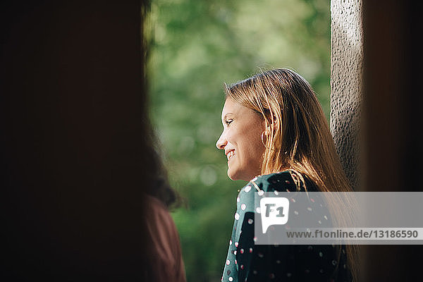 Smiling young woman in balcony looking away during party