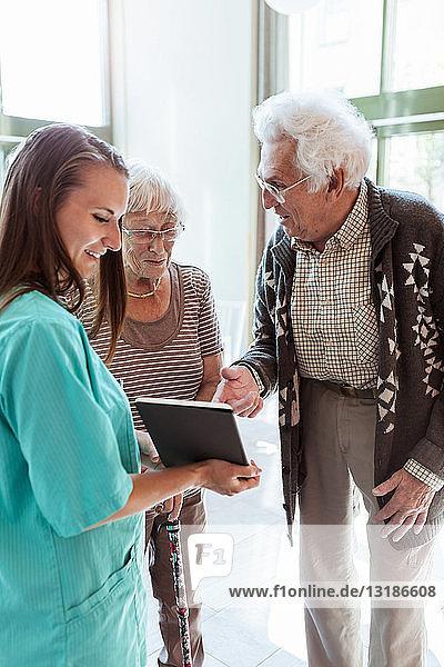 Junge Krankenschwester zeigt digitales Tablett einem älteren Paar im Pflegeheim