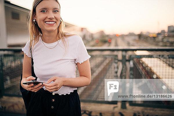 Porträt einer lächelnden jungen Frau  die ein Smartphone in der Hand hält  während sie auf einer Brücke in der Stadt steht
