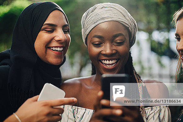 Glückliche multiethnische Freundinnen  die im Hinterhof stehen und auf ihr Handy schauen