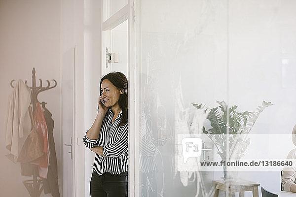 Kreative Geschäftsfrau  die an der Tür des Sitzungssaals steht und mit dem Handy telefoniert