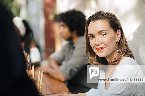 Portrait of confident woman sitting at table in balcony