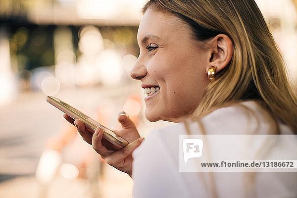 Lächelnde junge Frau hält Handy in der Hand  während sie draußen in der Stadt sitzt