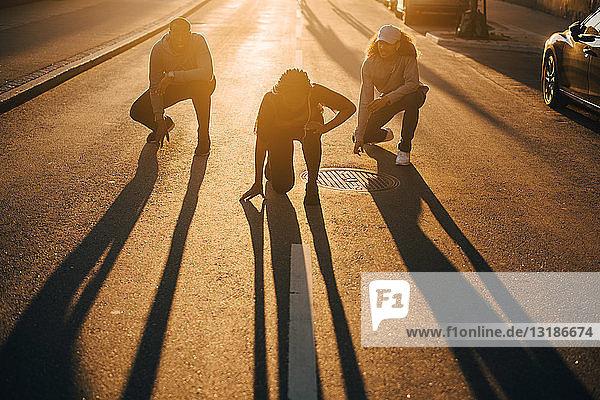 Freunde in voller Länge  die bei Sonnenuntergang im Sonnenlicht auf der Straße tanzen
