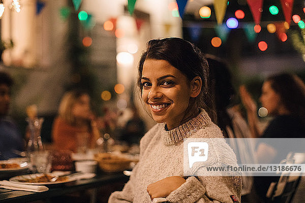 Porträt einer lächelnden jungen Frau  die während einer Dinnerparty im Hinterhof am Tisch sitzt