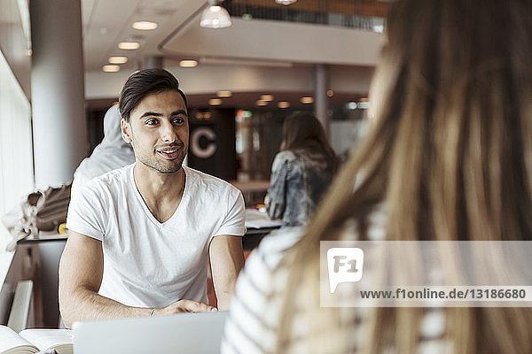 Lächelnder Mann diskutiert mit Freundin während des Studiums an der High School