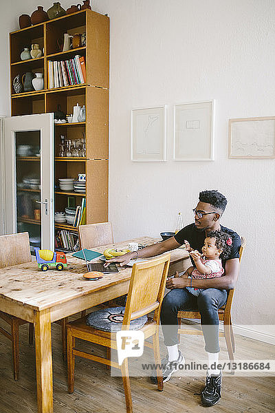 Young man using laptop while sitting with daughter on chair at dining table in house