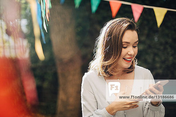 Smiling young woman using mobile phone while standing in backyard