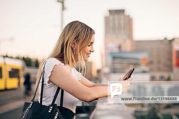 Seitenansicht einer jungen Frau  die ein Mobiltelefon benutzt  während sie sich an das Geländer einer Brücke in der Stadt lehnt