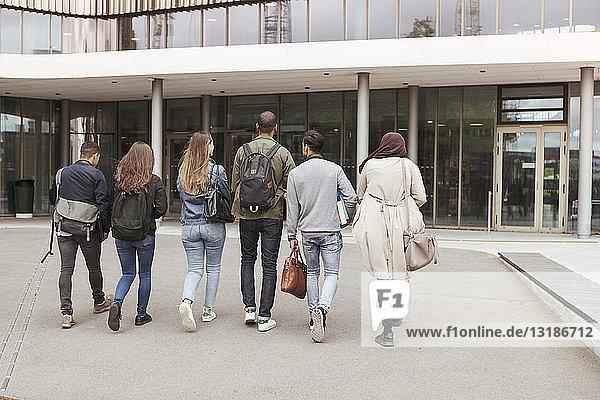 Rückansicht von multiethnischen Schülern  die gegen Gebäude auf dem High-School-Campus laufen