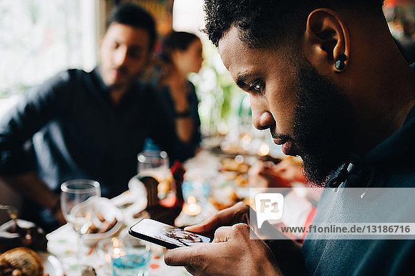 Young man photographing lunch while sitting with friends at restaurant during party