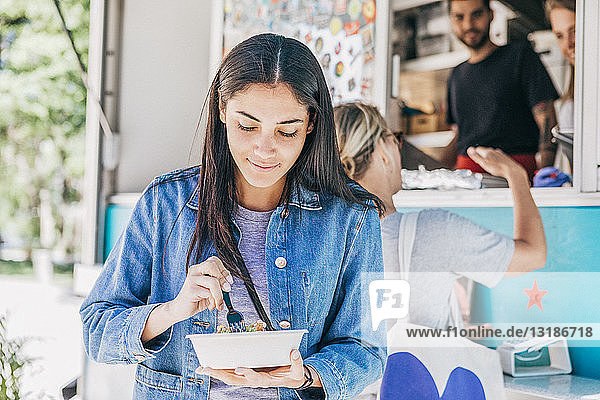 Young woman eating fresh Tex-Mex in bowl against food truck