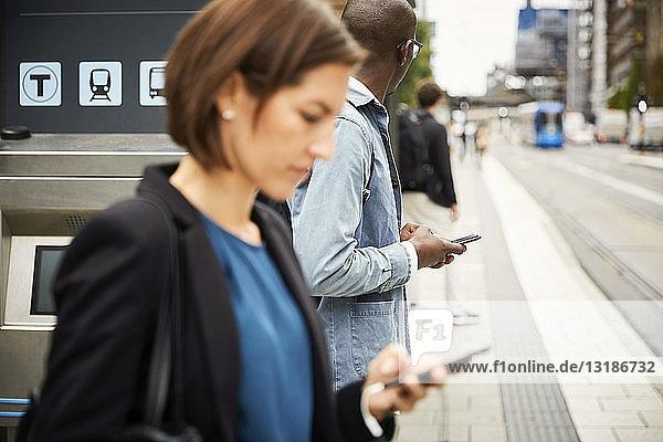 Pendler mit Smartphone beim Warten auf dem Bürgersteig in der Stadt