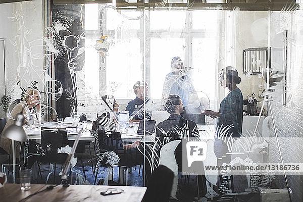 Kreative Geschäftsleute beim Brainstorming im Konferenzraum durch gemustertes Glas gesehen