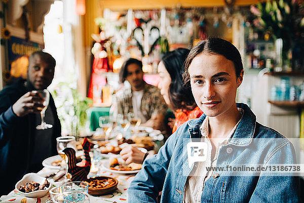 Porträt einer selbstbewussten jungen Frau  die während der Dinnerparty im Restaurant gegen Freunde am Tisch sitzt