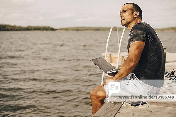 Nachdenklicher  reifer Mann sitzt mit Laptop auf dem Steg über dem See