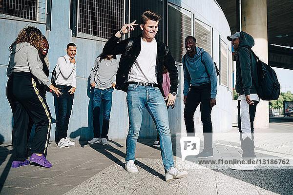 Fröhliche Freunde betrachten einen jungen Mann  der in der Stadt auf dem Bürgersteig steht