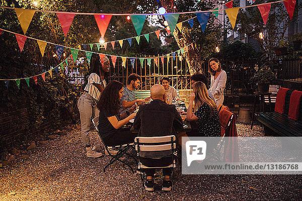 Multi-ethnische Freunde beim Abendessen während einer Gartenparty im Garten