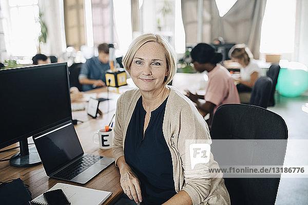 Porträt einer selbstbewussten reifen Geschäftsfrau  die am Computerschreibtisch im Kreativbüro sitzt