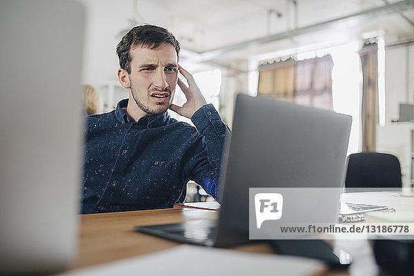 Verwirrter Geschäftsmann schaut auf Laptop  während er im Büro am Schreibtisch sitzt