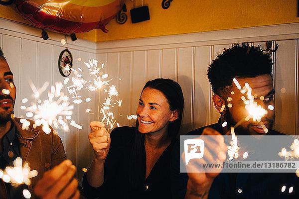 Lächelnde junge Frau mit multiethnischen männlichen Freunden  die während der Dinnerparty im Restaurant Wunderkerzen halten