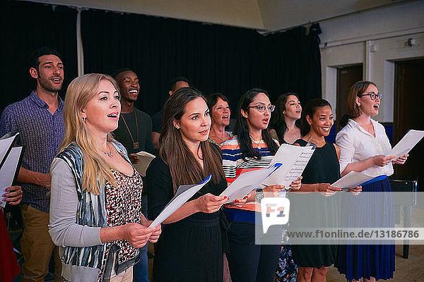 Männliche und weibliche Freunde üben Chor auf der Bühne im Auditorium