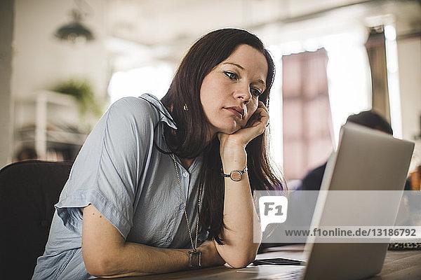 Angespannte Geschäftsfrau schaut auf den Laptop  während sie im Kreativbüro am Schreibtisch sitzt