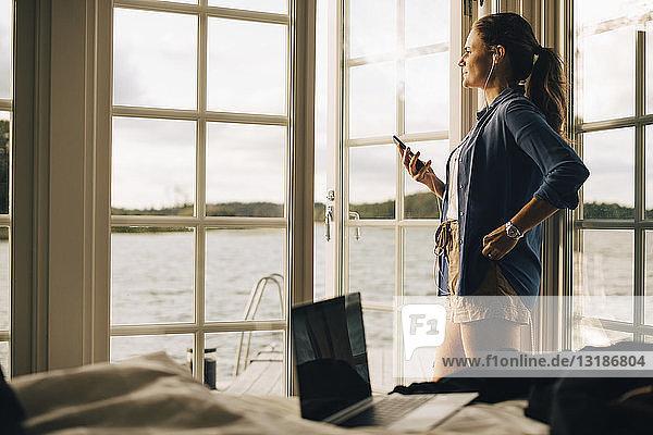 Nachdenkliche reife Frau  die in der Ferienvilla Musik über Kopfhörer am Smartphone hört