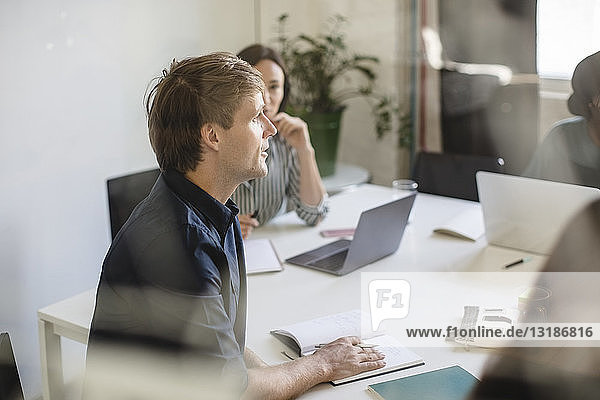 Businessman discussing with colleagues during meeting in office