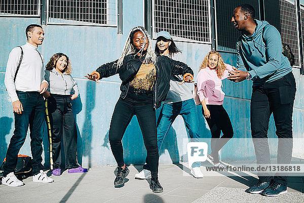 Lächelnde Freunde betrachten Teenager-Mädchen  die in der Stadt auf dem Bürgersteig tanzen