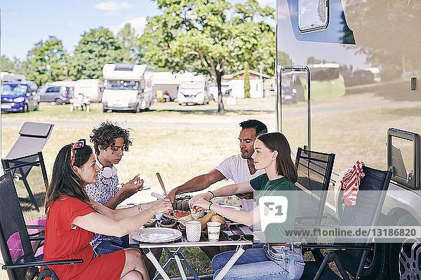 Familie geniesst Essen am Tisch  während sie vor dem Wohnmobil im Wohnwagenpark sitzt