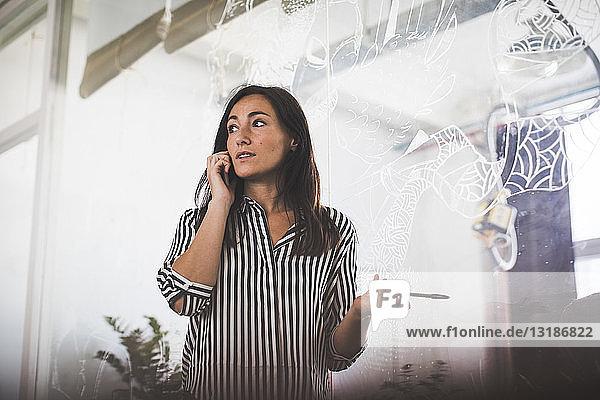Kreative Geschäftsfrau schaut weg  während sie mit dem Handy gegen den Sitzungssaal telefoniert