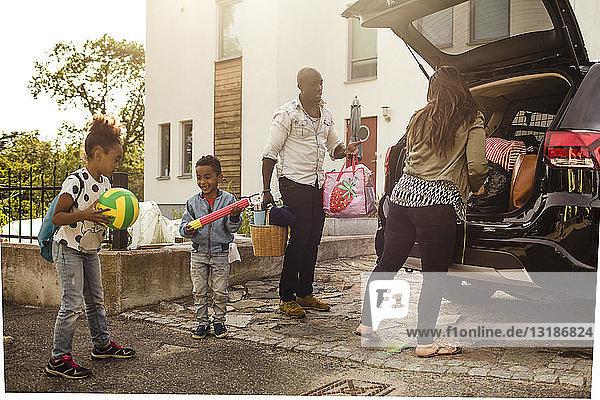 Familie in voller Länge mit Elektroauto auf Einfahrt gegen Haus