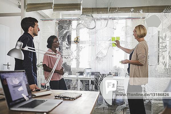 Kreative Geschäftsfrau erklärt Kollegen über Haftnotizen im Büro