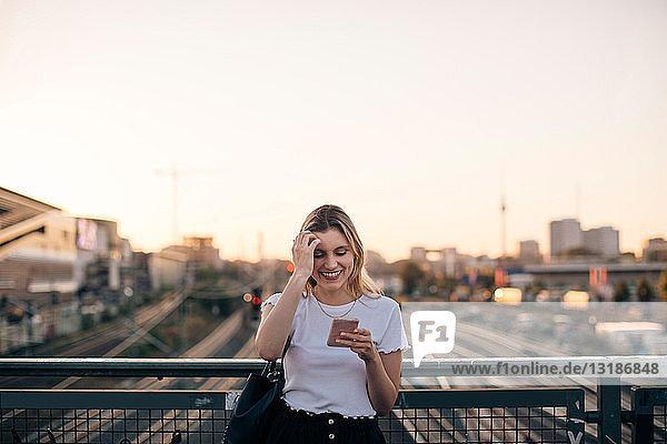 Lächelnde junge Frau benutzt Smartphone auf der Brücke gegen den klaren Himmel während des Sonnenuntergangs in der Stadt