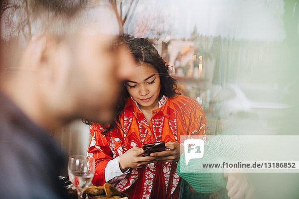 Junge Frau benutzt ein Smartphone  während sie mit Freunden im Restaurant sitzt und durch ein Glasfenster gesehen wird